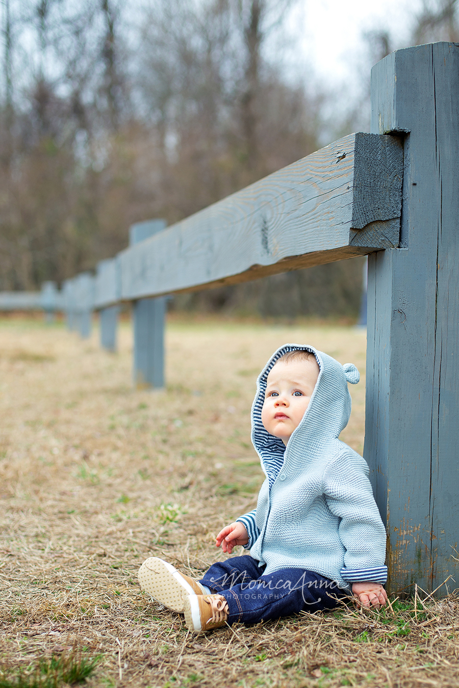 NJ Family Photographer Baby boy sitting up against wooden fence